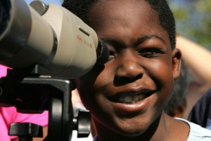 afro-american-boy-face-child-enjoys-the-view-through-the-lens-of-a-binocular-725x483